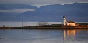 Hvit kirke, på et nes, sjø, sommer