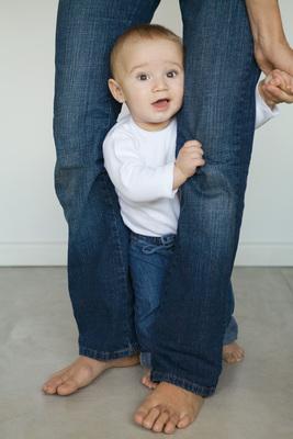 Liten gutt mellom bena til voksen