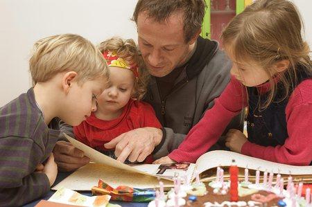 Barn og mannlig ansatt ser i bok