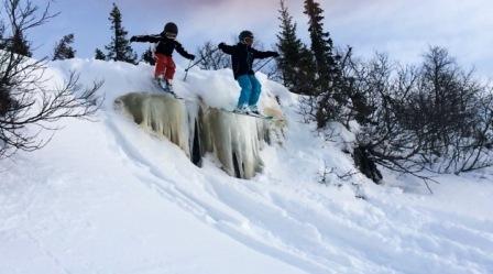 Unger hopper på ski over issvull