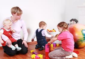 Barn og voksne rundt bord i barnehagen