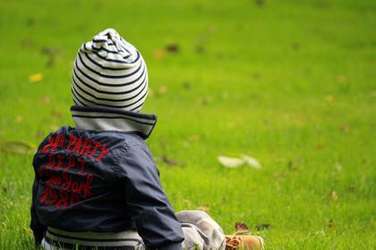 Liten gutt bakfra i grønt gress