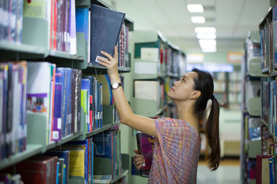 44141886 - library ,women student find book for study.