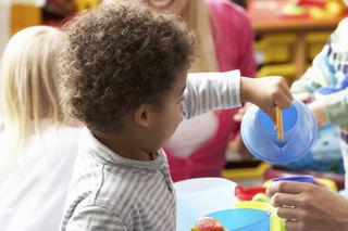 Barn med stripete genser leker med tekanne