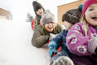 Glade barn som aker i snøen