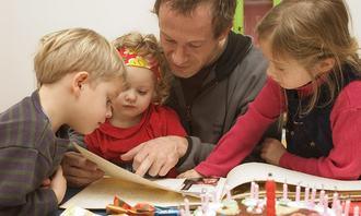 Tre barn og mann leser bok