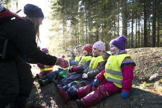 Barnehagebarn sitter på stein i skogen