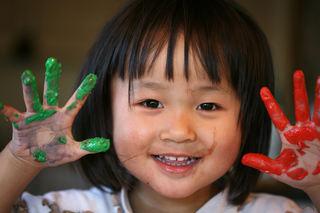 Asiatisk jente med maling på hendene