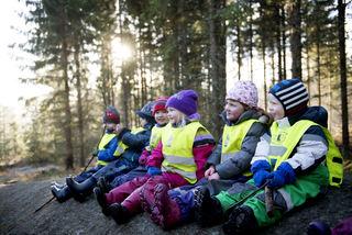 Barnehagebarn sitter på rekke i skogen