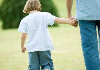 Gutt som holder voksen i hånden, sett bakfra