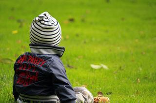 Liten gutt som sitter i gresset, sett bakfra