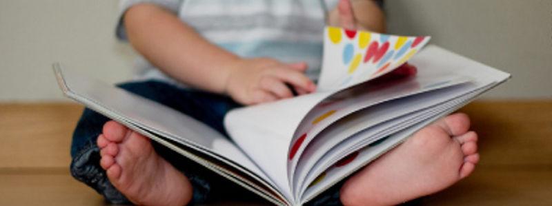 Eit lite barn med open bok på beina