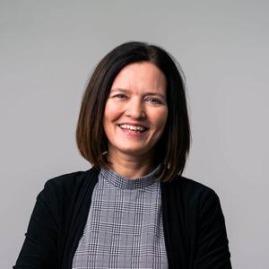 Bilde av en smilende dame med mørkt halvlangt hår