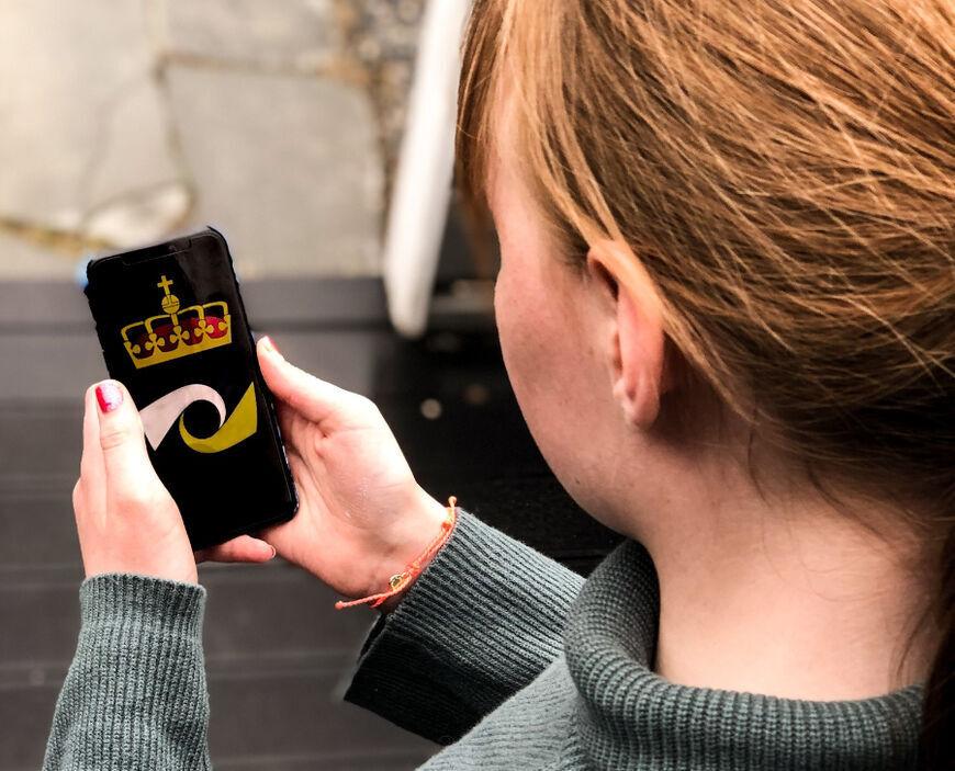 Person med telefon med logoen til kriminalomsorgen