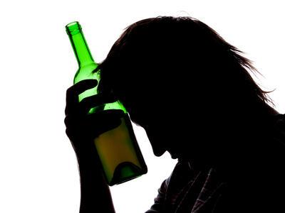 Silhuett av person som holder en flaske inn mot hodet. Illustrasjonsbilde.