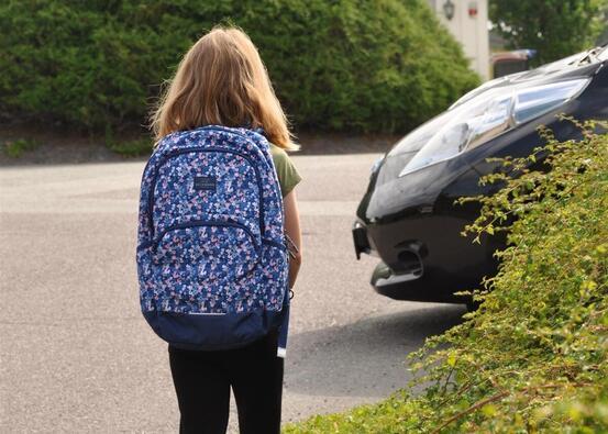 Skoleelev går på uoversiktlig vei på grunn av vegetasjon i veikanten.