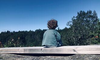 ENSOMT BARN: Gutt med krøllete hår sitter alene og ser ut i den store verden.