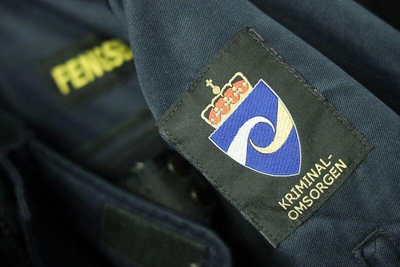 Uniform med kriminalomsorgens emblem