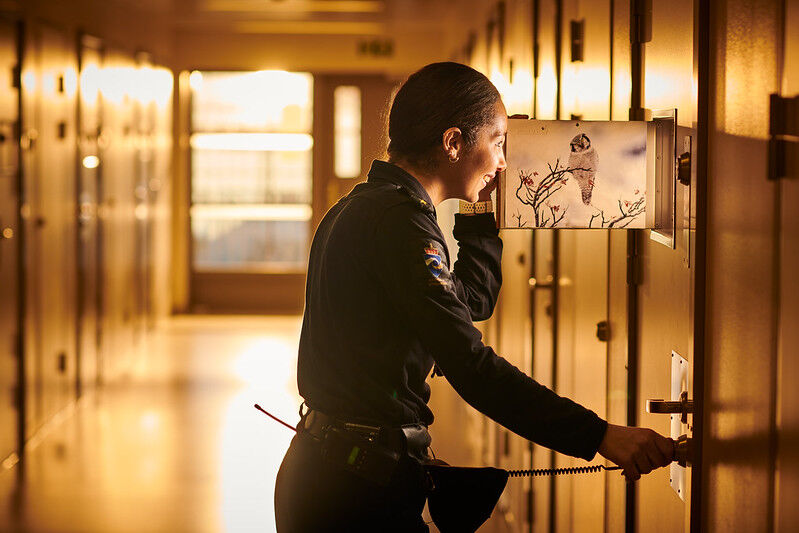 Betjent ser inn gjennom dørluke