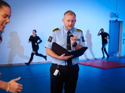 Fysisk test, instruktør fra KRUS teller runder og oppmuntrer. Illustrasjonsfoto.