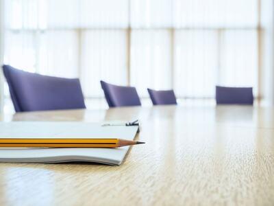 Bilde av et konferanserom med et stort avlangt bord og stoler som passer til styremøte