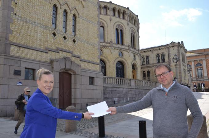 Lene Vågslid tar imot forslaget fra Audun Bringsvor foran Stortinget. Foto: Sigbjørn Larsen