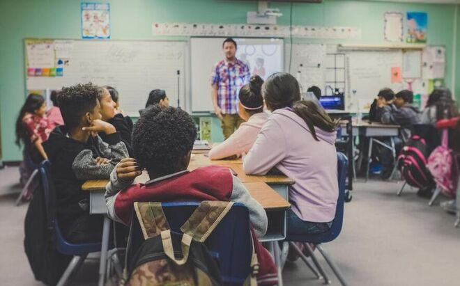 Foto som viser lærer i klasserom med elever