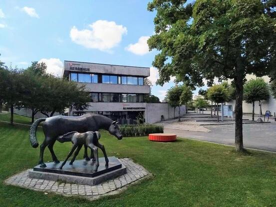 Foto av Ås råhus med innbyggertorget og skulpturen Hoppe med føll