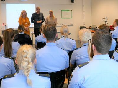 Kursledere oppstilt foran aspiranter i klasserom. Foto.