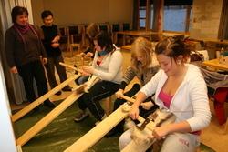 Elever skraper reinskinn mens klasselærer Ingebjørg Iversen og duodjilærer Vigdis Siri ser på.